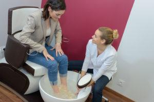 Frau bekommt ein Fußbad zur Fußpflege in München